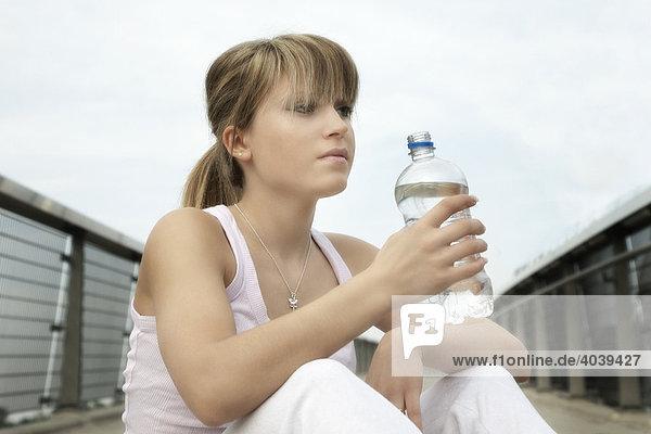 Junge Frau mit Wasserflasche löscht nach dem Sport ihren Durst