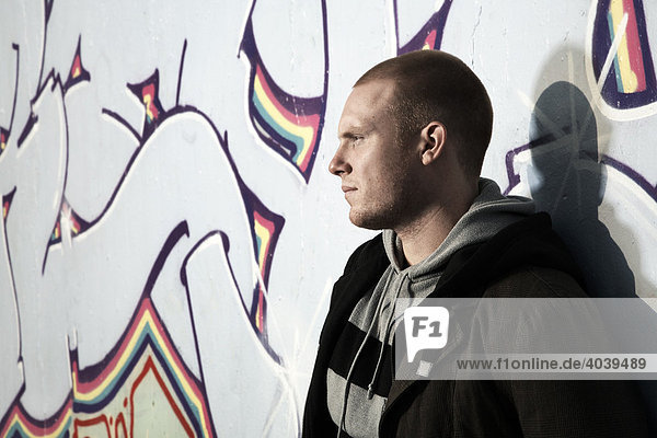 Young man leaning against a graffiti wall  portrait