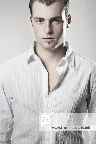 Portrait of a young man wearing a white shirt looking into camera