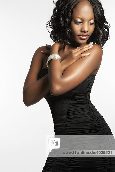 Portrait of a young dark-skinned woman in a black dress  arms crossed over her chest  eyes on the ground