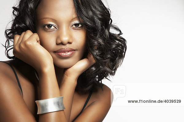 Portrait of a young dark-skinned woman  hand on cheek  looking into the camera