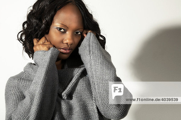Portrait of a young dark-skinned woman wearing a grey knitwear top with hands on her cheeks