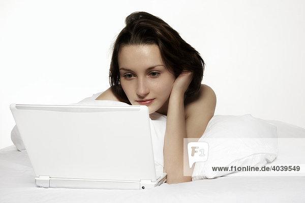 Junge brünette Frau arbeitet mit ihrem Laptop im Bett