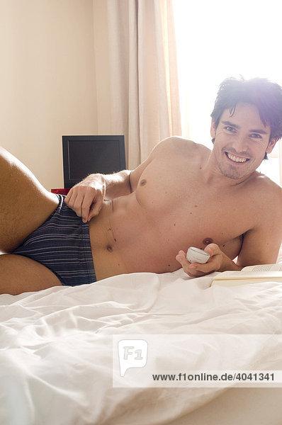 Mann in Unterwäsche im Bett