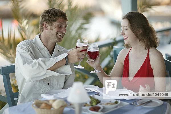 Liebespaar stößt mit Rotwein an