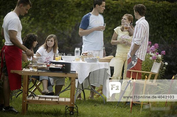 Gruppe junger Leute beim Barbecue im Garten