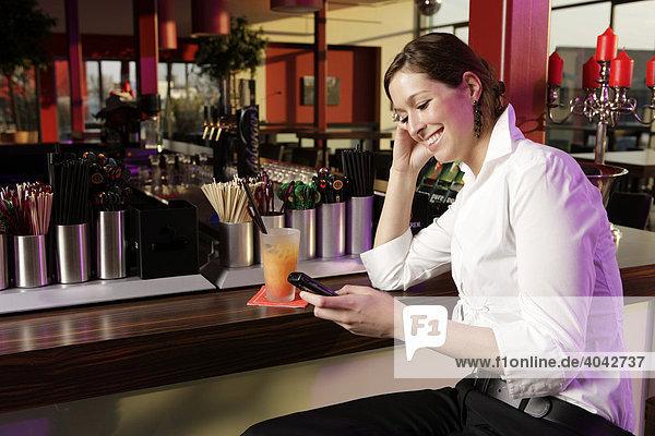 Junge Frau mit Mobiltelefon in einer Bar