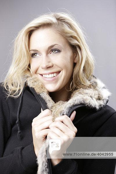 Junge blonde Frau in schwarzer Jacke