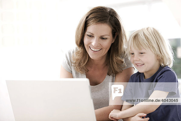 Blonde son and mother using a laptop  laughing