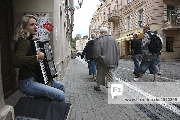 Accordion playing young blond female street musician and pedestrians in the historic centre of Vilnius  capital of Lithuania  Baltic States  North East Europe