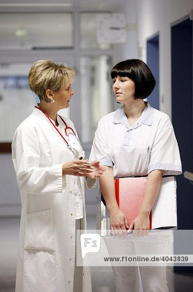 Female doctor talking to a nurse in a hospital ward corridor