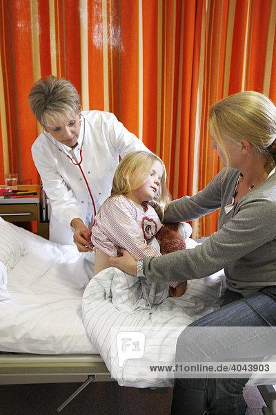 Ärztin untersucht eine junge Patientin  7 Jahre  gestützt von der Mutter  im Krankenbett in einem Krankenhaus