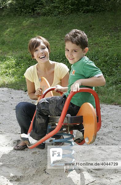 Junge Mutter und Sohn  Kind auf dem Spielplatz