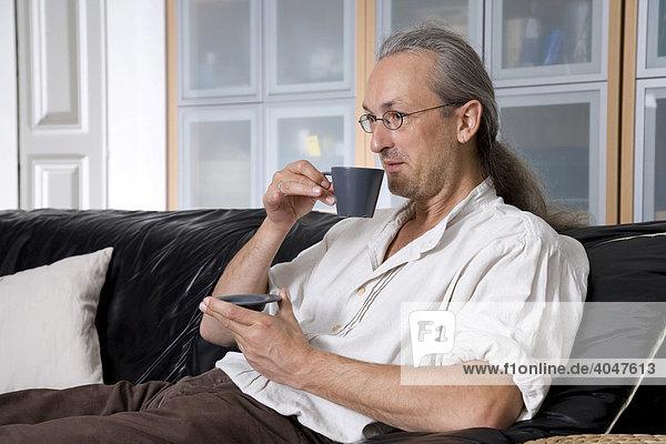 Mann trinkt auf Sofa gemütlich Kaffee
