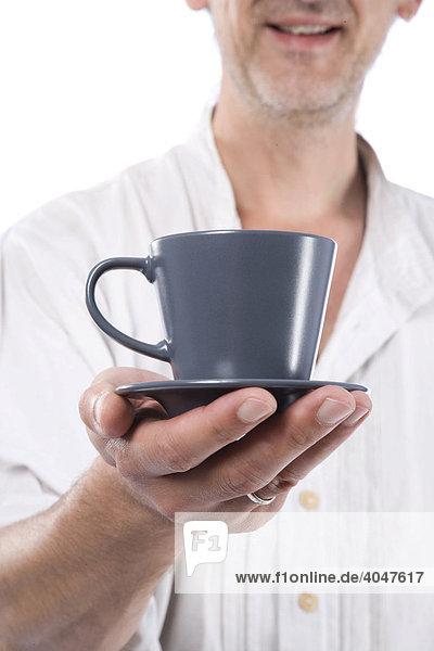 Mann hält graue Kaffeetasse