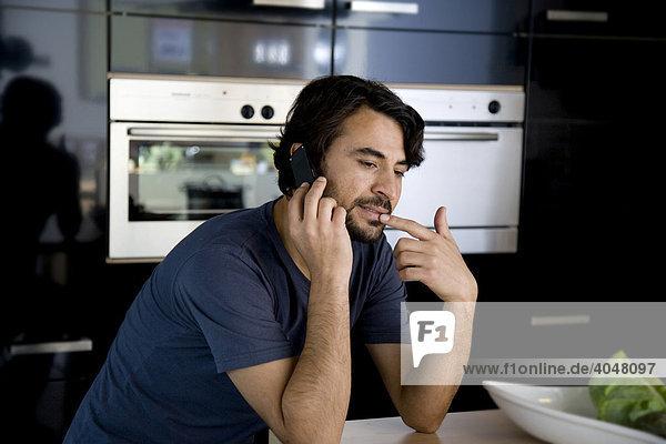 Mann telefoniert in der Küche mit Handy