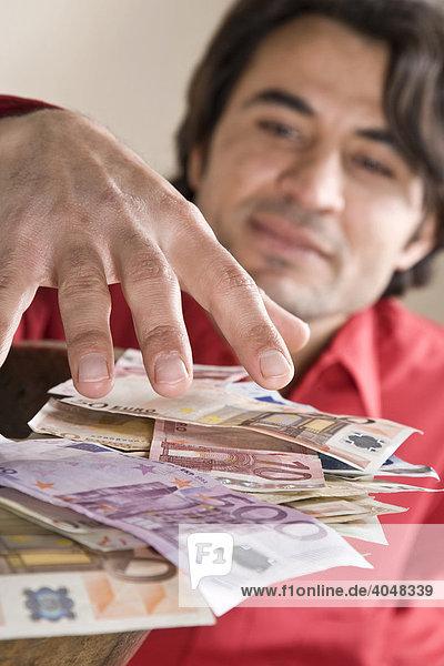 Man grabbing at a pile of money