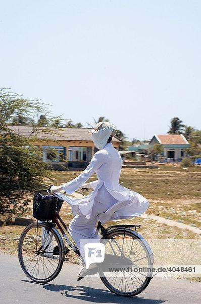 Frau auf Fahrrad mit der traditionellen vietnamesischen Tracht Ao Dai  Phan Thiet  Binh Thuan  Vietnam  Asien