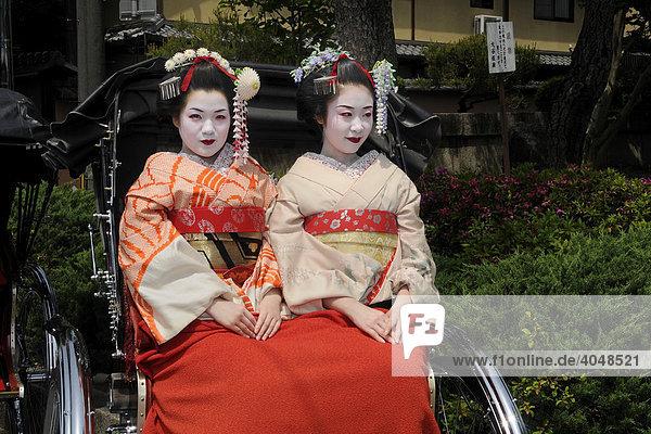 Maikos  apprentice Geishas  on a rickshaw tour through the historic city centre of Kyoto  Japan  Asia