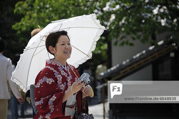 Japanerin mit Kimono  Sonnenschirm und Fotoapparat in einem Tempel in Kyoto  Japan  Asien
