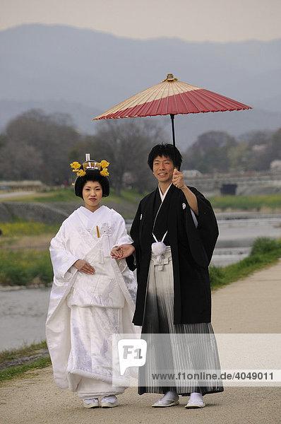 Traditionelles japanisches Hochzeitspaar im Kimono mit Hochzeitsfrisur der Braut und traditionellem Papiersonnenschirm am Kamigamo Fluss in Kyoto  Japan  Asien