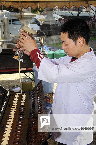 Mann bei der Herstellung von Backwaren am Kintano Schrein auf dem Trödelmarkt  Kyoto  Japan  Asien