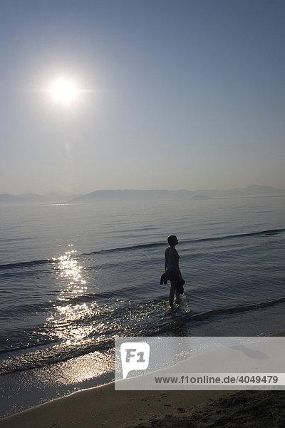 Junge Frau im Gegenlicht beim Strandspaziergang