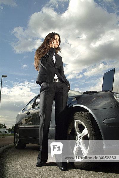 Junge telefonierende Geschäftsfrau am Auto mit Laptop vor Wolkenhimmel