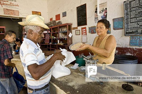 Cuban receiving food for his food vouchers from a saleswoman in a store  Trinidad  Sancti-Spíritus Province  Cuba  Latin America  America
