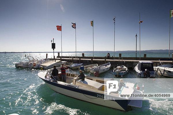 Ein Motorboot mit Touristen verlässt den Hafen  Sirmione  Gardasee  Lago di Garda  Lombardei  Italien  Europa