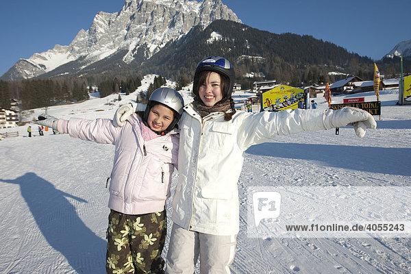 Zwei Skliläuferinnen stehen auf der Skipiste und freuen sich  hinten die Zugspitze  Tirol  Österreich  Europa