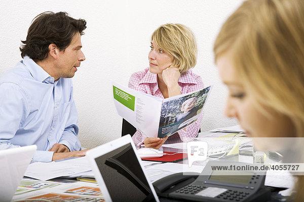 Mitarbeiterin und Mitarbeiter einer Werbeagentur beim Diskutieren einer Werbebroschüre und von Entwürfen für eine Werbekampagne  Zürich  Schweiz  Europa