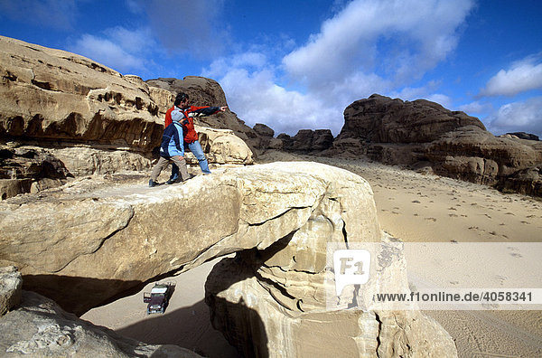Father and son standing on a stone bridge  Wadi Rum  Jordan  Middle East