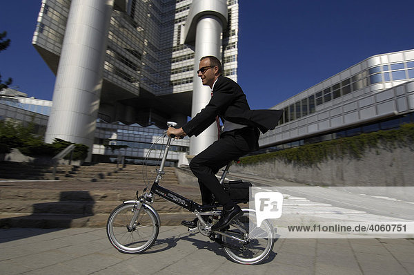Businessman mit Faltrad auf dem Weg zur Arbeit  Hypobank-Hochhaus  Bogenhausen  München  Bayern  Deutschland  Europa