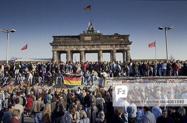 Fall der Berliner Mauer: Menschen aus Ost- und West-Berlin sind auf die Mauer am Brandenburger Tor geklettert  Berlin  Deutschland  Europa Fall der Berliner Mauer: Menschen aus Ost- und West-Berlin sind auf die Mauer am Brandenburger Tor geklettert, Berlin, Deutschland, Europa