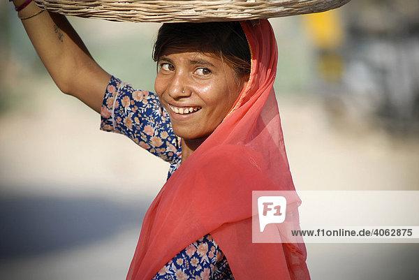 Junge Frau trägt Korb auf dem Kopf  Pokaran  Rajasthan  Nordindien  Indien  Asien