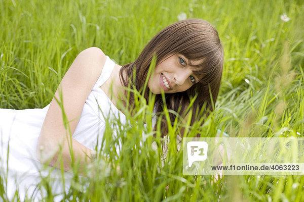 Junge dunkelhaarige Frau mit weißem Kleid genießt auf einer grünen Wiese liegend den Sommer