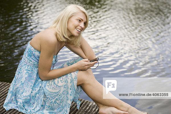 Junge blonde Frau sitzt in einem Kleid auf einem Steg am Wasser und hört Musik