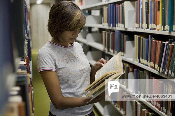 Junge dunkelhaarige Frau  Studentin  blättert in einem Buch zwischen den Bücherregalen in der Bibliothek