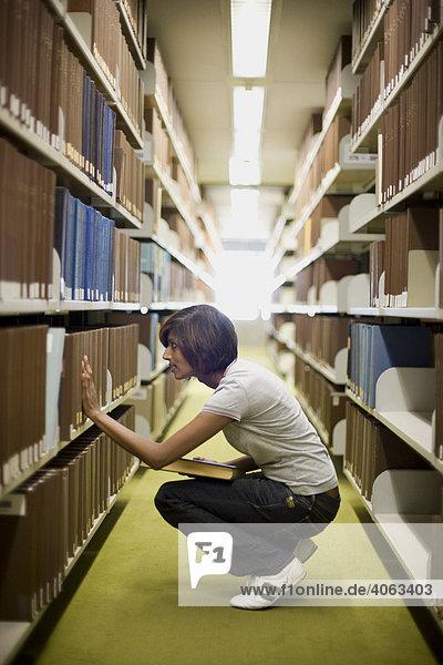 Junge dunkelhaarige Frau  Studentin  greift nach einem Buch aus einem Bücherregal in der Bibliothek
