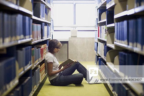 Junge dunkelhaarige Frau  Studentin  sitzt zwischen den Bücherregalen in der Bibliothek und liest in einem Buch