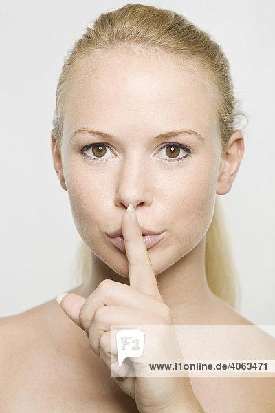 Junge blonde Frau mit Zeigefinger vor dem Mund bittet um Ruhe