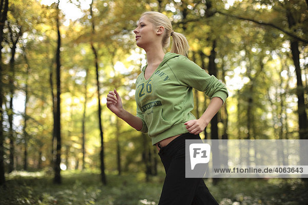 Young blonde woman jogging in the autumnal forest