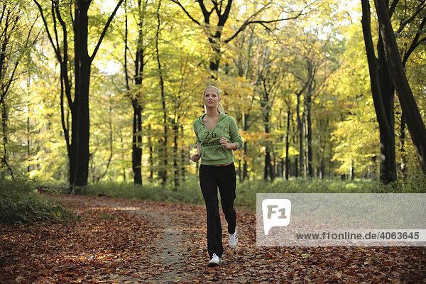 Junge blonde Frau beim Laufen im herbstlichen Wald