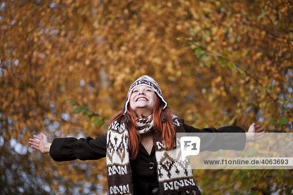 Junge rothaarige Frau mit Mütze und Schal genießt mit ausgebreiteten Armen den Herbst