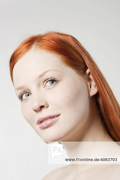 Portrait of a young red-haired woman in front of white backdrop