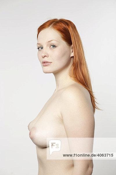 Junge rothaarige Frau mit unbekleidetem Oberkörper vor Weiß Junge rothaarige Frau mit unbekleidetem Oberkörper vor Weiß