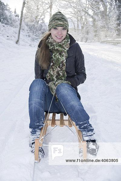 Junge Frau fährt mit einem Schlitten im Schnee
