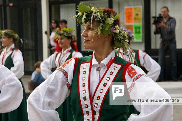 Folkloregruppe in Trachten tanzt beim Mittsommerfest in