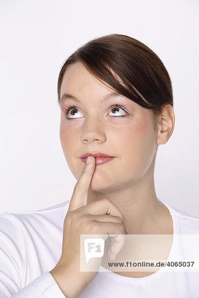 Mädchen  15 Jahre  überlegt  mit Finger am Mund